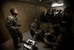"""Pilots, medics, and crew chiefs share a laugh in one of Charlie Company's ready-rooms. Scenes from the medical evacuations of wounded Americans, Canadians, and Afghan civilians and soldiers being flown by Charlie Co. 6th Battalion 101st Aviation Regiment of the 101st Airborne Division. Charlie Co. - which flies under the call-sign """"Shadow Dustoff"""" - flies into rush the wounded to medical care out of bases scattered across Oruzgan, Kandahar, and Helmand Provinces in the Afghan south. These images were taken of missions flown out of Kandahar Airfield in Kandahar Province and Camp Dwyer in Helmand Province."""