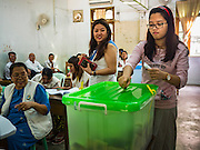 08 NOVEMBER 2015 - YANGON, MYANMAR:  A woman drops her completed ballot into a ballot box in her voting place in a public school in central Yangon. The citizens of Myanmar went to the polls Sunday to vote in the most democratic elections since 1990. The National League for Democracy, (NLD) the party of Aung San Suu Kyi is widely expected to get the most votes in the election, but it is not certain if they will get enough votes to secure an outright victory. The polls opened at 6AM. In Yangon, some voters started lining up at 4AM and lines were reported to long in many polling stations in Myanmar's largest city.     PHOTO BY JACK KURTZ