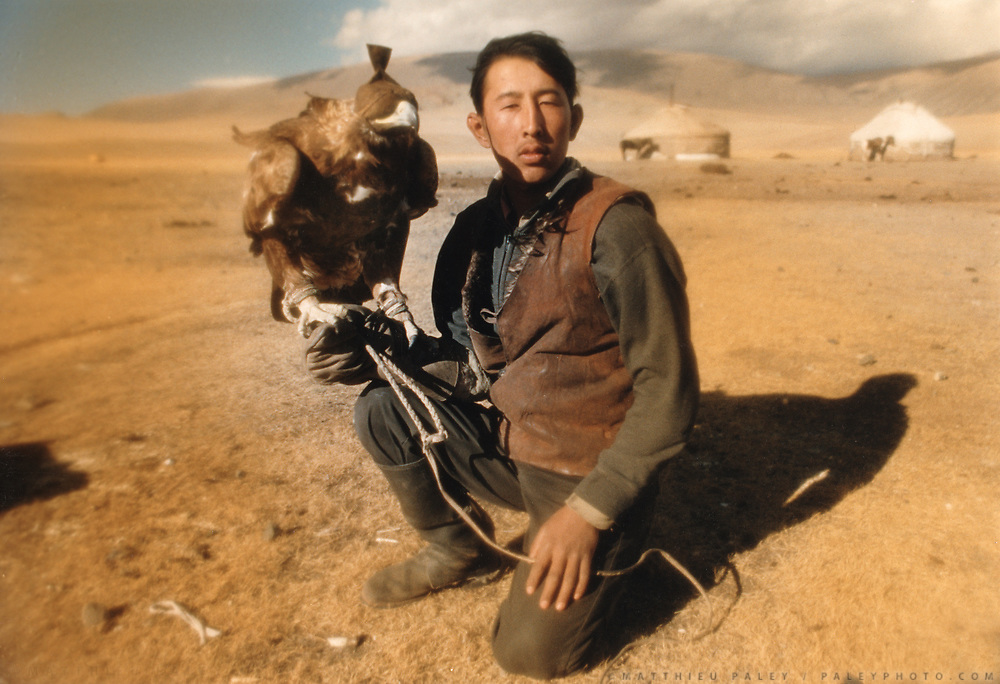 A young man proudly displays his eagle beside his yurt. Eagles, blinded in order not to bite its owner, are used to hunt to catch rabbits, baby wolves, marmots etc. The fur of these animals are sold in towns.