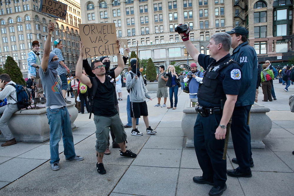 Anti-Nato protest in Chicago, a protesters holds up a sign with a George Orwell quote while being filmed by the police