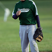 A young baseball player blows a bubble with his bubble gum during the Norwalk Little League baseball competition at Broad River Fields,  Norwalk, Connecticut. USA. Photo Tim Clayton