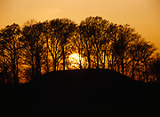 Sun setting beyond earthwork mound built by people of the Plum Bayou Culture, Lower Mississippi Valley, Toltec Mounds Archeological State Park, Arkansas.