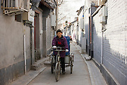 Woman delivering bottled beers on a tricycle cart, Hutongs area, Beijing, China