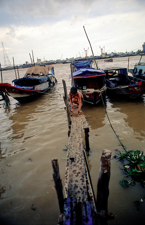 A teenager fixes a jetty that takes him across to his fishing boat on the Saigon river, District 2 of Ho Chi Minh City. 2007.