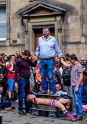 Edinburgh Scotland 7th August 2016 :: Performers from Fringe shows entertain in the High Street to promote their shows.<br /> <br /> Pictured:  Spikey Will a professional speciality act juggler and street performer entertains crowds in the High Street, assisted by three members of the public.<br /> <br /> (c) Andrew Wilson   Edinburgh Elite media
