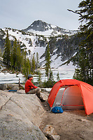 Backpacker relaxing in backcountry camp at Mirror Lake, Eagle Cap Wilderness Oregon