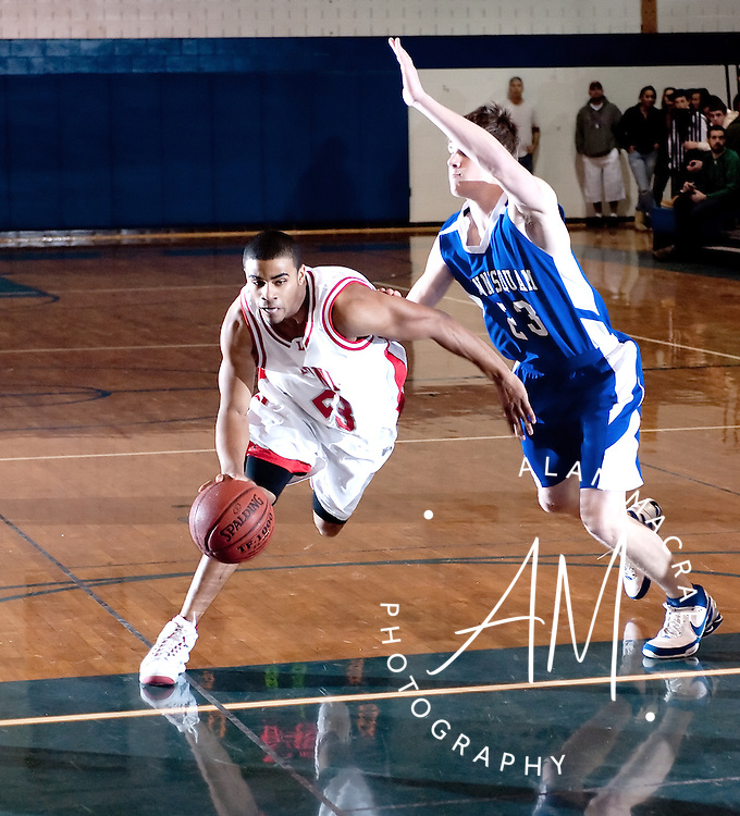 Laconia's Christian Birt presses past Winnisquam's Derick Jenness in Saturday's game during the 35th Annual Gilford Holiday Basketball Tournament.  (Alan MacRae/for the Citizen)