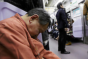 elderly male person asleep in train Tokyo Japan