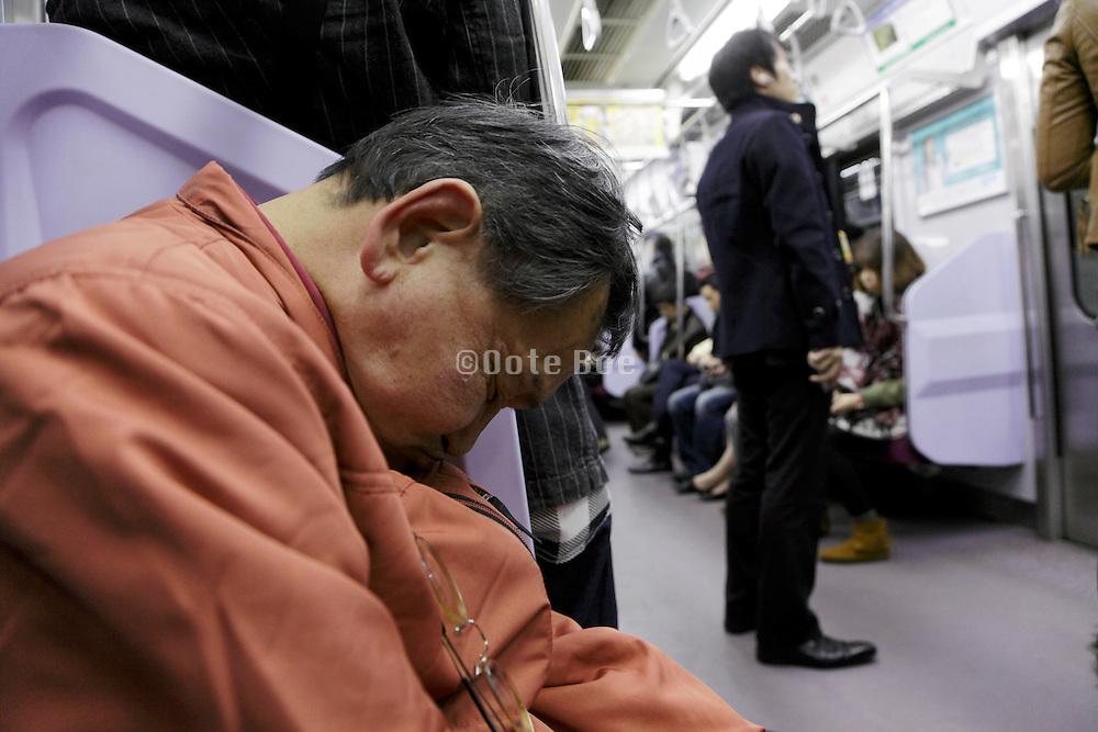 elderly male person asleep in train Tokyo Japan