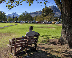 March 19, 2011 - Stellenbosch, Western Cape, South Africa - A local inhabitant rests on a bench on The Braak (Village green) in Stellenbosch. Laid out in 1703 as a parade ground, today it lies at the center of the oak-lined streets, water canals and beautiful Cape Dutch architecture of the second oldest European settlement in the Western Cape province of South Africa in the heart of the Cape Winelands. In background the Groot Drakenstein and Simonsberg mountains can be seen. (Credit Image: © Arnold Drapkin/ZUMAPRESS.com)
