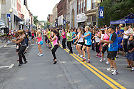 Middletown, New York - People on North Street participate in a Zumba in the Street warmup before the 2012 Run 4 Downtown road race on Saturday, Aug. 18, 2012.
