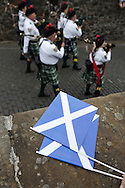A Scottish saltire lying on a wall as a traditional Scottish pipe band marches past during Pipefest Stirling, an event staged at Stirling Castle to coincide with the 700th anniversary of the Battle of Bannockburn. The event was attended by 1600 pipers, Highland dancers and other musicians and formed a procession through the city's streets. The Battle of Bannockburn took place in 1314 and resulted in the defeat of Edward II's English army by the Scots under Bruce.
