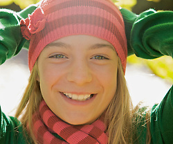 Close up of a  smiling young girl with her hands on her head wearing a woolly hat