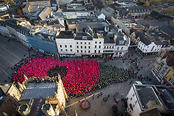 "© Licensed to London News Pictures 11/11/2018, Cirencester, UK. People gather to form a world record breaking (pending conformation) ""human poppy"" in Cirencester town Market Place to commemorate the end of the First World War 100 years ago today. Over 3,300 people wore coloured ponchos to create the shape of a poppy and leaf. Photo Credit : Stephen Shepherd/LNP"