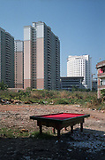 A pool table stands in an empty lot near new apartment buildings in Shenzhen, China in December, 2008.  Pool is a popular past time among China's migrant work force..