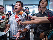 """14 FEBRUARY 2015 - BANGKOK, THAILAND: Student activist Siriwit Serithiwat talks to reporters after he was detained by police during a protest the military coup. Martial law is still in effect in Thailand and protests against the coup are illegal. Dozens of people gathered in front of the Bangkok Art and Culture Centre in Bangkok Saturday to hand out red roses and copies of George Orwell's """"1984."""" Protestors said they didn't support either Red Shirts or Yellow Shirts but wanted a return of democracy in Thailand. The protest was the largest protest since June 2014, against the military government of General Prayuth Chan-Ocha, who staged the coup against the elected government. Police made several arrests Saturday afternoon but the protest was not violent.      PHOTO BY JACK KURTZ"""