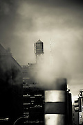 View of a water tank above the smoke of a street pipe from West Broadway avenue in Tribeca, Manhattan, New York, 2009.