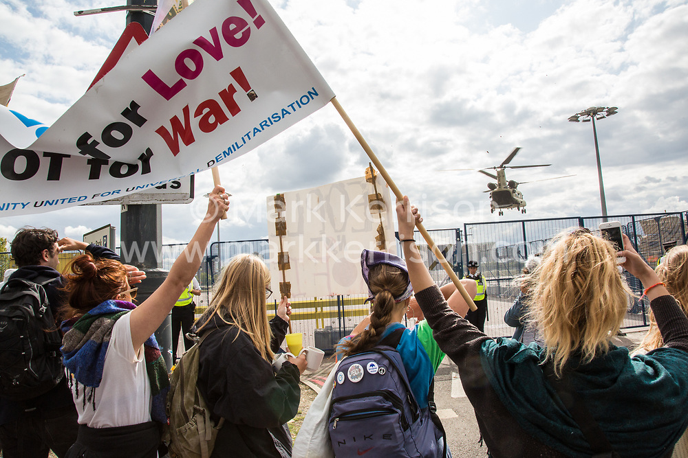 London, UK. 7 September, 2019. Activists observe a military helicopter landing outside ExCel London during the sixth day of Stop The Arms Fair protests against DSEI, the world's largest arms fair. The sixth day of protests was billed as a Festival of Resistance and included performances, entertainment for children and workshops as well as activities intended to disrupt deliveries to ExCel London for the arms fair.