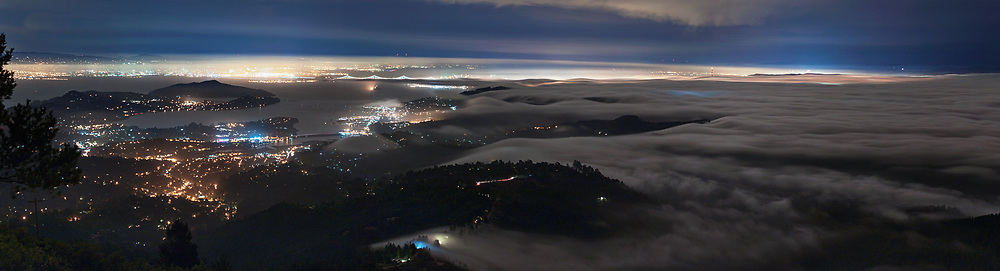 The San Francisco Bay area is seen at night from the Summit of Mount Tamalpais in Marin County. Fog blankets the majority of Sausalito, Marin City and Mill Valley below, as Oakland, Tiburon and the SF-Oakland Bay Bridge poke through the misty night.