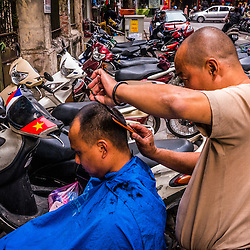 """Outdoor Barber, Hanoi. <br /> <br /> During the time of economic recession, legions of self-taught hairdressers from various corners of the city ventured downtown, transforming an entire Hanoian boulevard into a """"barber-street"""". Many ex-soldiers were encouraged to be creative in those harsh years, thus to sustain their livelihood. Despite being citywide popular, the arising modernisation (cars/ shops) of the capital in the late 90's abolished the barber-streets forever, forcing the figaros to scatter elsewhere. Some of them opened their own salons, many applied for other jobs, and a handful still remains in the business until now to keep up the Hanoian hair-cult."""