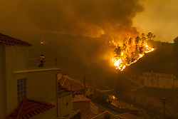 June 18, 2017 - Pampilhosa da Serra, Portugal - A wildfire creeps over a hill at night in Pampilhosa da Serra, a town in the Coimbra district, as a resident watches from the roof of the village chapel. A raging forest fire in central Portugal killed at least 62 people as they desperately tried to flee, charring cars and trucks as it swept over roads. The disaster is the worst tragedy Portugal has experienced in decades. (Credit Image: © Atlantico Press via ZUMA Wire)