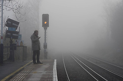 © Licensed to London News Pictures. 11/12/2013. London, UK. Londoners stand in a heavy fog at Tooting Rail station during the morning rush hour.  Photo credit : Richard Isaac/LNP