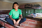 A young Nepalese orphan sits on the top bunk in his bedroom in the Voice of Children rehabilitation center in Kathmandu, Nepal. The not-for-profit organisation supports street children and those who are at risk of sexual abuse through educational and vocational training opportunities, health services and psychosocial counseling. This boy also lives in the center while he is part of the rehabilitation program and hopes to be fostered.