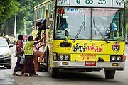 19 JUNE 2013 - YANGON, MYANMAR: A conductor leans out of a bus to help passengers board at a stop in Yangon. Yangon buses are generally overcrowded and in poor repair but as the economy improves newer, but still used, Japanese and Korean buses are being imported. Hundreds of bus routes criss-cross Yangon, providing the cheapest way of getting around the city. Most fares are less than the equivalent of .20¢ US.   PHOTO BY JACK KURTZ