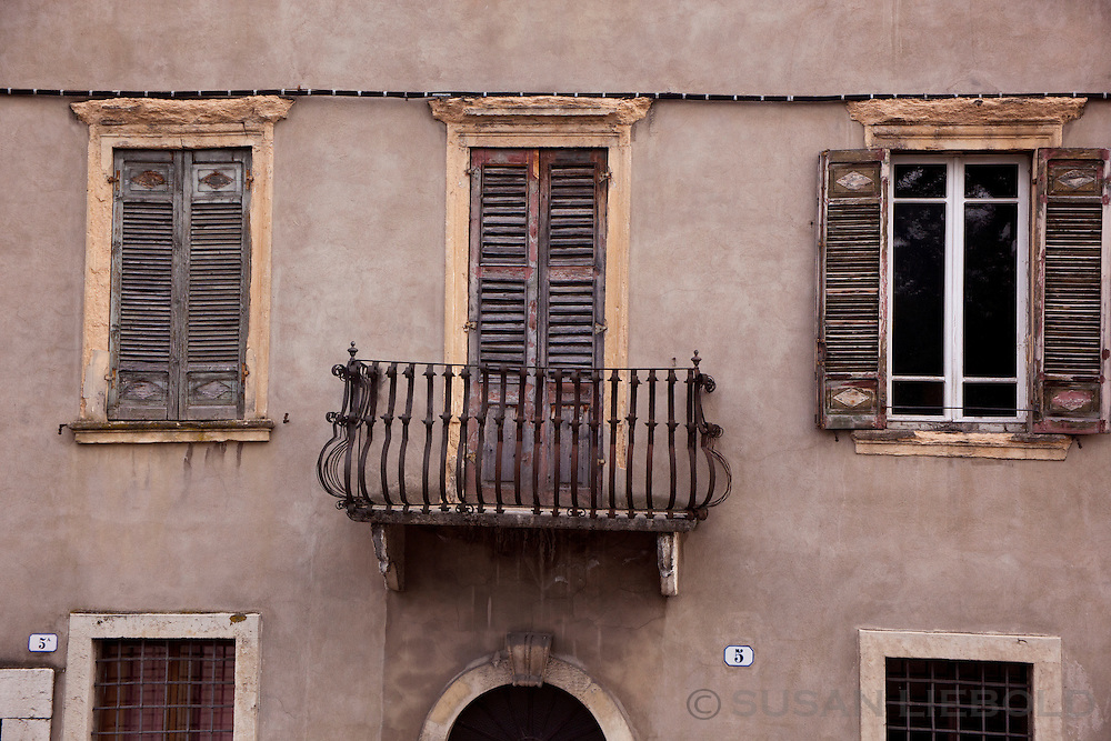 A small balcony and two windows on the side of a building in Verona, Italy.