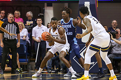 Dec 1, 2019; Morgantown, WV, USA; West Virginia Mountaineers forward Oscar Tshiebwe (34) makes a move in the lane while defended by Rhode Island Rams forward Jermaine Harris (0) during the first half at WVU Coliseum. Mandatory Credit: Ben Queen-USA TODAY Sports