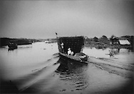 Fishing boat laden with nets returns to the floating villlage of Kampong Khleang after nightfall, Tonle Sap, Cambodia.
