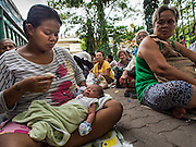"""07 AUGUST 2014 - BANGKOK, THAILAND:     A woman and her child wait for food distribution to start at Pek Leng Keng Mangkorn Khiew Shrine. Thousands of people lined up for food distribution at the Pek Leng Keng Mangkorn Khiew Shrine in the Khlong Toei section of Bangkok Thursday. Khlong Toei is one of the poorest sections of Bangkok. The seventh month of the Chinese Lunar calendar is called """"Ghost Month"""" during which ghosts and spirits, including those of the deceased ancestors, come out from the lower realm. It is common for Chinese people to make merit during the month by burning """"hell money"""" and presenting food to the ghosts. At Chinese temples in Thailand, it is also customary to give food to the poorer people in the community.  PHOTO BY JACK KURTZ"""