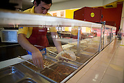 .An employee puts ingredients in a flour tortilla at the new Burritos Crisostomo in El Paso Texas on Sunday morning, Oct. 11, 2009..