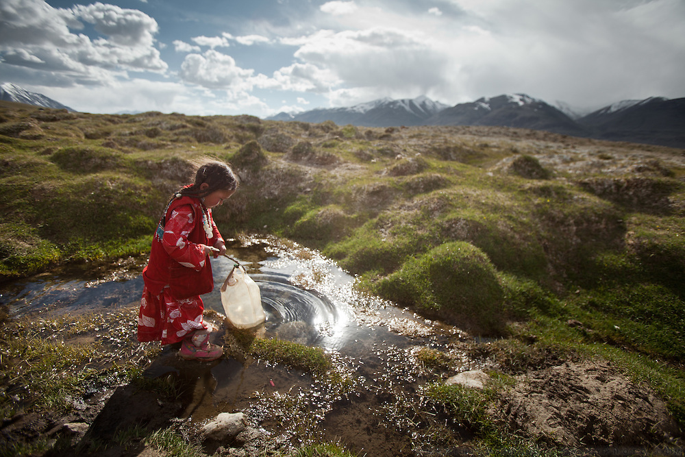 Six-year old Susaï is fetching water near camp in a spring claimed as one of the sources of the Oxus, also known as Amu Darya, Central Asia's largest river.  Its waters define most of Afghanistan's borders with other nations to the north..