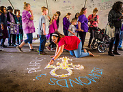 21 APRIL 2017 - CHANHASSEN, MN: TAYLOR HEPLER, from Harrisburg, PA, makes a memorial to Prince in the pedestrian tunnel in front of Paisley Park, his former home and recording studio. The tunnel has become a memorial to Prince, people have drawn graffiti in the tunnel honoring him and they leave memorials in the tunnel. The superstar died from an accidental overdose of the opioid fentanyl on April 21, 2016. Friday was the first anniversary of his death. Crowds of people gathered at Paisley Park, which is now a museum, to honor the Minnesota born musician.     PHOTO BY JACK KURTZ