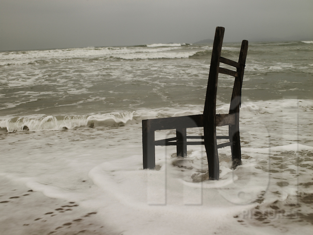 Ocean waves crash against a decaying wooden chair stuck in the sand, Hoi An, Vietnam, Southeast Asia
