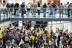 © Licensed to London News Pictures. 24/07/2021. Manchester, UK. Anti-lockdown protesters March through the Arndale centre in central Manchester. Protests have been organised in over 200 cities as part of a 'World Wide Rally for Freedom', calling for an end to lockdowns, the wearing of face masks and mandated vaccinations. Photo credit: Adam Vaughan/LNP