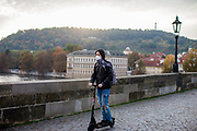 A young man on a electric scooter wearing a face mask on Charles Bridge in Prague. As of 21st of October 2020 people have to wear face masks outside and inside.
