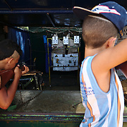 Young boys practicing shooting at a street stand