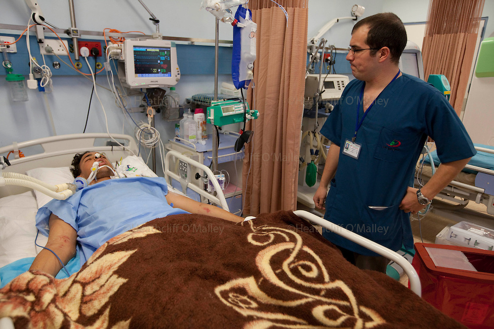 Mcc0030300 . Sunday Telegraph..Abdelbaset Senussi being tended to by Anglo/Libyan Dr Omar Bushiha in one of the main hospitals in Benghazi..Abdelbaset  lost both his legs from an exploding Libyan government shell whilst sitting outside his home with 4 of his six brothers in the beseiged town of Ajdabiyah, 150 kms from Benghazi. Two of his brothers lost their lives, the other two are in the same hospital and have also lost limbs...Benghazi 25 March 2011