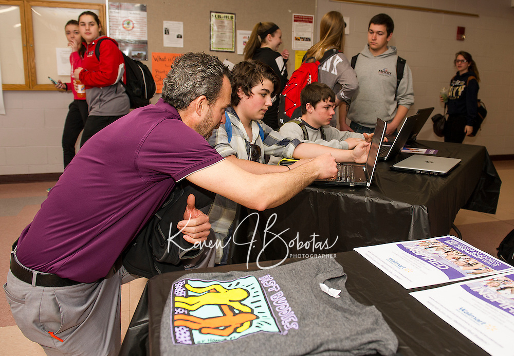 "Special Education teacher Alex Takantjas helps Carter Dutton and Jake Deware sign up for the ""Best Buddies"" program at Belmont High School Thursday morning.  (Karen Bobotas/for the Laconia Daily Sun)"