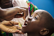 A nurse gives vitamin A supplement to Lacine, 4, who suffers from malaria and diarrhea, during a consultation at the Libreville health center in Man, Cote d'Ivoire on Wednesday July 24, 2013.