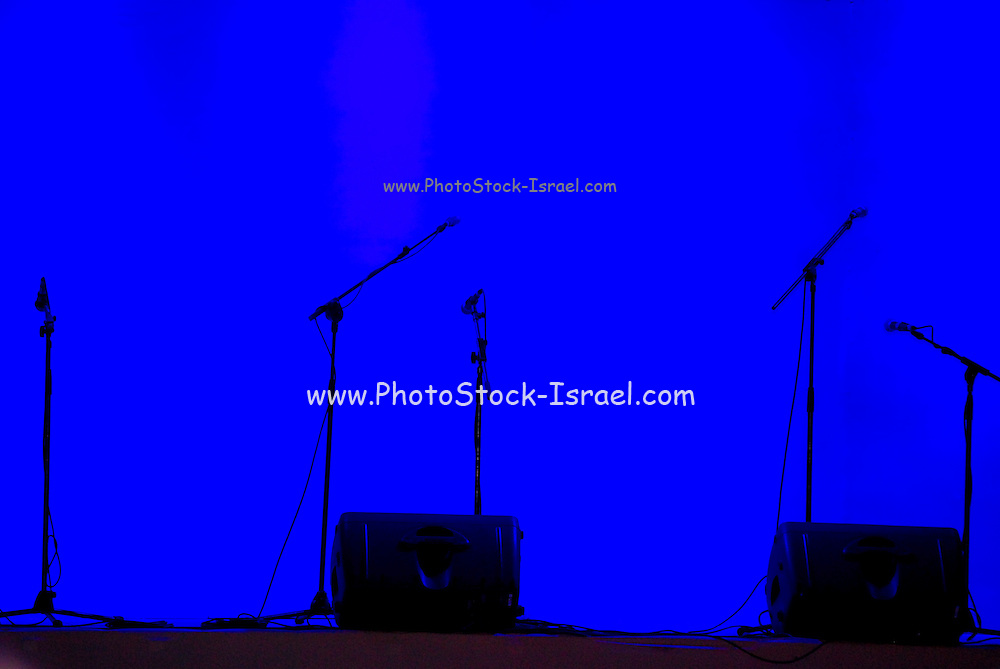 silhouette of microphones on an empty stage, dark blue background