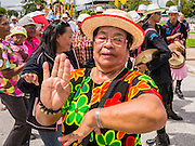 31 OCTOBER 2012 - YALA, YALA, THAILAND: Women from Wat Kohwai dance in the streets of Yala for Ok Phansa. Ok Phansa marks the end of the Buddhist 'Lent' and falls on the full moon of the eleventh lunar month (October). It's a day of joyful celebration and merit-making. For the members of Wat Kohwai, in Yarang District of Pattani, it was a even more special because it was the first time in eight years they've been able to celebrate Ok Phansa. The Buddhist community is surrounded by Muslim villages and it's been too dangerous to hold the boisterous celebration because of the Muslim insurgency that is very active in this area. This the year the Thai army sent a special group of soldiers to secure the village and accompany the villagers on their procession to Yala, a city  about 20 miles away.   PHOTO BY JACK KURTZ