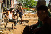 06 SEPTEMBER 2013 - BANGKOK, THAILAND: Workers relax in front of their homes at a construction site in the Bang Na section of Bangkok near Suvarnabhumi International Airport. The workers are building a four storey apartment building. They will live on the site for approximately one year, until the building is close to opening. They are paid the Thai minimum wage of 300 Baht per day, approximately $10 US. They live on the site rent free and don't pay to use electricity, both are provided by the project owner.               PHOTO BY JACK KURTZ