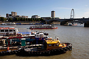 Scene of the River Thames, London. Running through the heart of the city. Barges boats and tugs with a view west.