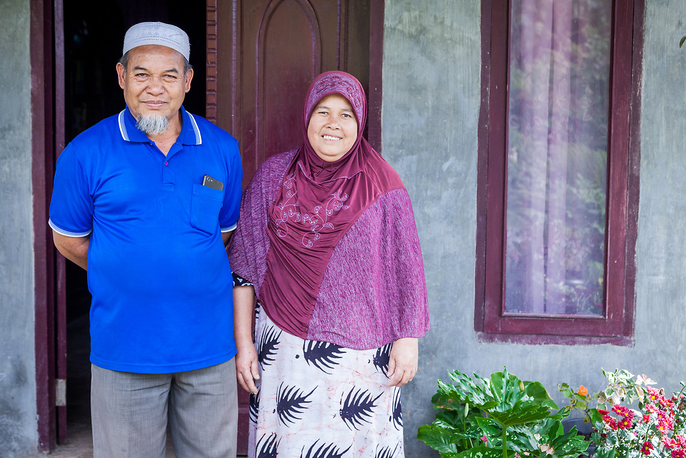 Pak Alda (60) and wife Ibu Isnaini (50) pose for a photo in front of their home.  Pak Alda has been a member of Tunas Indah for 4 years.  The biggest obstacles as a farmer is the rainy season and the instability of coffee price.  The quality of coffee depends on the efforts that farmers put into it.  As a coffee farmer, he is most proud of the quality and the excellent tastes of his coffee.  As a member of Tunas Indah he receives permium, coffee seeds, and support.  Fair traide means transparency and equal benefits and consumers will get quality coffee that tastes great.