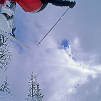 A young skier leaps off of a powder-covered bump at Montana's Big Sky resort.