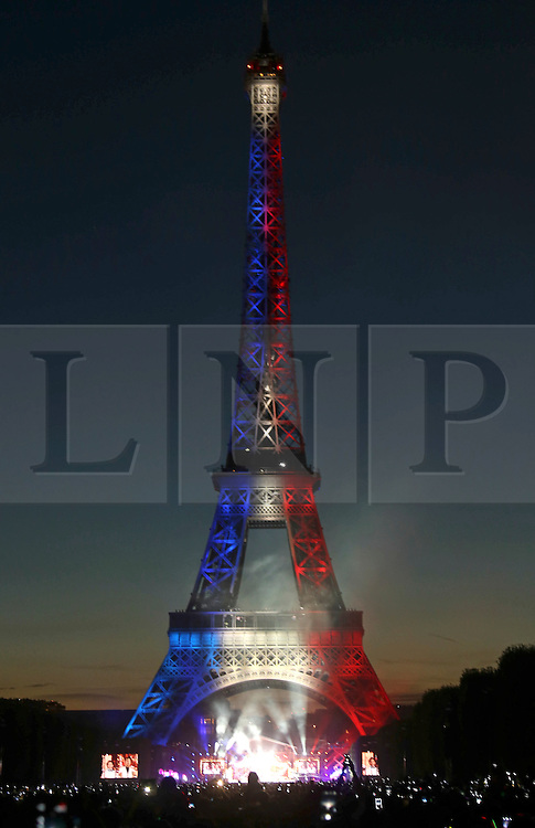 © Licensed to London News Pictures. 14/07/2015. Paris, FRANCE.  The Eiffel Tower in Paris lit in the clouds of the tricolour, the French Flag  during a firework display to celebrate Bastille Day on 14, July 2015. Photo credit: Jason Bryant/LNP