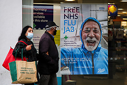 © Licensed to London News Pictures. 26/10/2021. London, UK. A couple wearing face coverings walk past a 'Free NHS Flu Jab' poster displayed in Boots pharmacy in Wood Green, north London. People are being urged to get their flu jab ahead of the winter as figures from the drug maker Reckitt suggest that the cold and flu season will be worse this year than normal. Health Secretary Sajid Javid is considering making flu jabs mandatory for all NHS staff.   Photo credit: Dinendra Haria/LNP